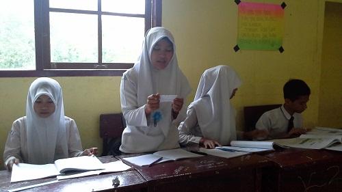 Salah seorang siswa sedang membacakan  pertanyaan dari bola salju dari kelompok lain