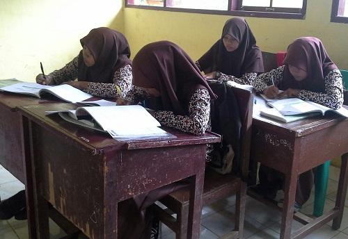 """Masing-masing siswa dalam kelompok sedang menyelesaikan tugas individu saat kegiatan """"THINK """" (BERFIKIR), dengan posisi duduk letter U ganda menghadap ke tengah kelas"""