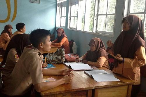 Salah seorang siswa mewakili kelompoknya mempresentasikan hasil diskusi interkelompoknya ke forum kelas