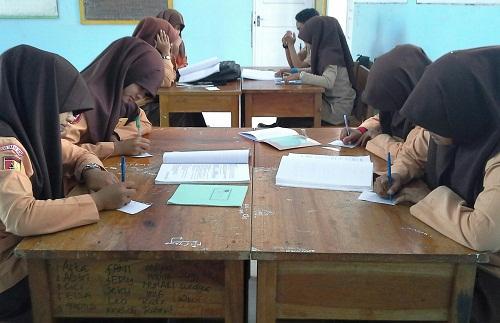 """Dokumentasi Foto pembelajaran ekonomi dengan Metode """"Everyone is Teacher Here"""", di mana terlihat siswa kelas XII-IS1 sedang membuat pertanyaan pada secarik kertas"""