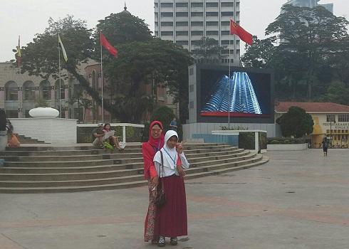 Dokumentasi Foto Penulis dan Siswa Bimbingan (Nessa Sapera) di Dataran Merdeka dengan latar bendera-bendera negara bagian Malaysia
